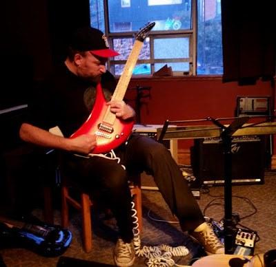 Musician Kurt Newman playing Red Guitar